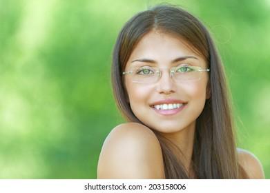 Face young beautiful girl dark closeups short hair glasses summer park smiling