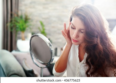 face of young beautiful healthy woman looking in the mirror