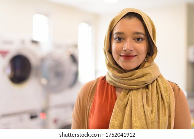 Face of young beautiful Indian Muslim businesswoman as owner of the laundromat