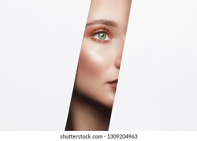 Face of a young beautiful woman with a bright makeup. make-up artist concept. A girl with beautiful bright eyes with shining shadows, looks into the hole of white paper
