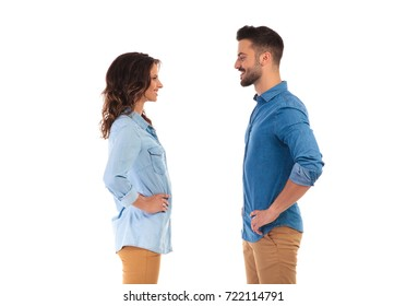 face to face young casual couple standing with hands on waist on white background