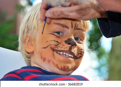 The face of a young child being made to look like a ferocious lion by a make-up artist