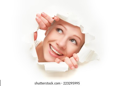 face of a young curious woman peeking through a  hole torn in white paper poster