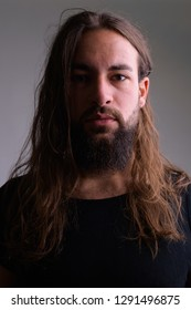Face of young handsome bearded man with long hair
