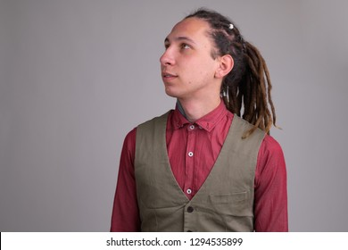Face of young handsome businessman with dreadlocks thinking