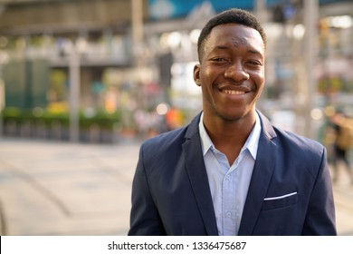 Face of young happy African businessman smiling in the city