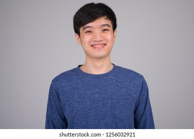 Face of young happy Asian man smiling against white background