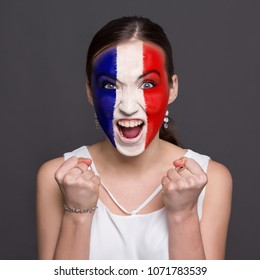 Face of young happy woman painted with flag of France. Football or soccer team fan, sport event, faceart and patriotism concept. Studio shot at gray background, copy space