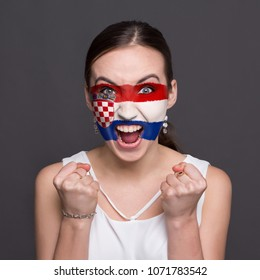 Face of young happy woman painted with flag of Croatia. Football or soccer team fan, sport event, faceart and patriotism concept. Studio shot at gray background, copy space