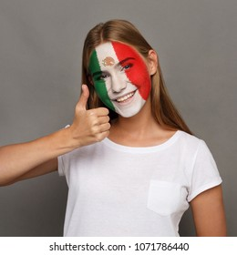 Face of young happy woman painted with flag of Mexica. Football or soccer team fan, sport event, faceart and patriotism concept. Studio shot at gray background, copy space