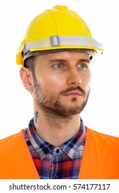 Face of young man construction worker thinking while looking at distance
