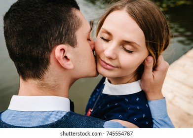 The face of young people. A couple standing, hugging, kissing on the background lake and on a wooden bridge. Close up. headshot, half length. A woman with Make-up her eyes closed.