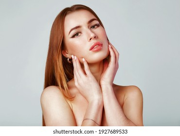 Face of the young pretty woman with a healthy skin. Beautiful face of young white woman with french manicure nail. Fashion makeup and care for hands , nails and cosmetics .