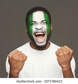 Face of young screaming african-american man painted with flag of Nigeria. Football or soccer team fan, sport event, faceart and patriotism concept. Studio shot at gray background, copy space