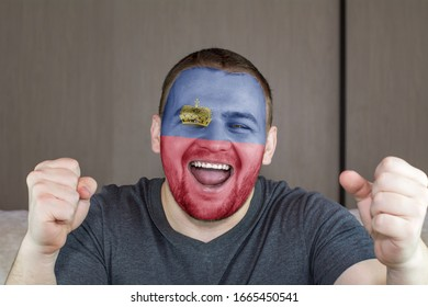 Face of young screaming man painted with flag of Liechtenstein. Football or soccer team fan, sport event, faceart and patriotism concept.