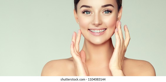Face of a young woman with braces on her teeth . Healthy smile