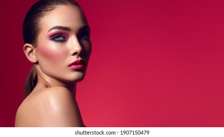 Face of a young woman with bright makeup on a pink background with gathered hair in a smooth ponytail.