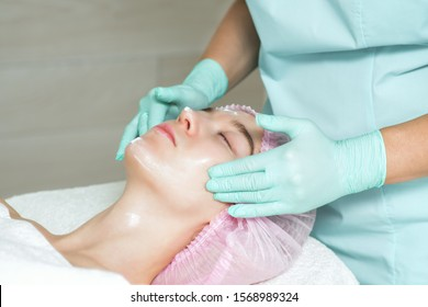Face of young woman with closed eyes is receiving a white cream in the spa beauty salon close up.