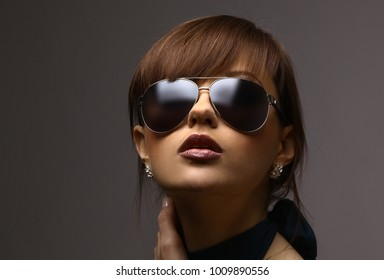 face of young woman in dark glasses.