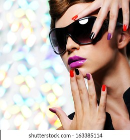 Face of young woman with  fashion manicure and black sunglasses