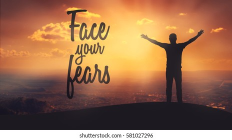 """Face your fears"" text on sunset background. Silhouette of man with raised hands on top of a mountain enjoying the view."