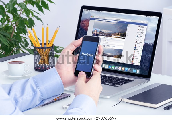 Facebook app on the Apple iPhone display and desktop version of Facebook on the Apple Macbook Pro Retina. Multi devices multitasking concept. All gadgets in full focus. Varna, Bulgaria - May 29, 2015.