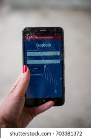 Facebook app problem. Facebook not responding. Facebook app on smartphone. Cracked screen smartphone in hand. Holding broken smartphone.