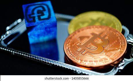 FACEBOOK logo on a blue wooden cube with two botcoin coins in golden and copper metal on a silver plastic tray. black background