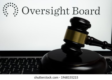 Facebook Oversight Board logo on the blurred background screen and judge gavel on the front. Concept. Stafford, United Kingdom, May 4, 2021