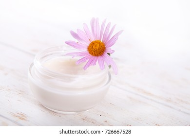 face-cream and flower on a white wooden background. natural organic cosmetic facial. space for text Close up