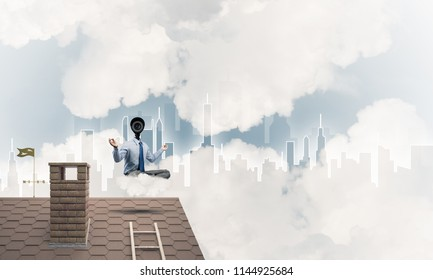 Faceless businessman with camera zoom instead of head sitting in lotus pose