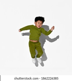 Faceless dark-haired boy jumping against the background of a white wall in the studio. The child is dressed in a stylish green tracksuit and white sneakers.