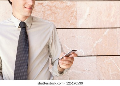 Faceless fashionable businessman wearing an elegant suit, leaning on a modern office building in the city and using a smart phone.