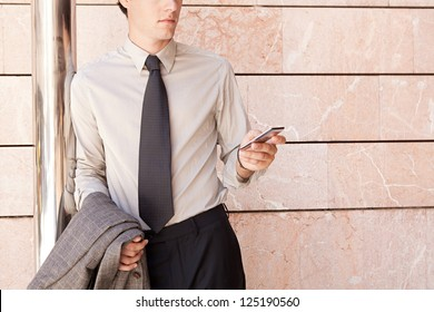 Faceless fashionable businessman wearing an elegant suit and shades, leaning on a modern office building in the city and using a smart phone.
