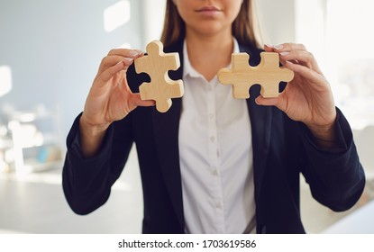 Faceless hands of a businesswoman with wooden puzzles in hands in the office.