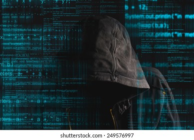 Faceless hooded anonymous computer hacker with programming code from monitor, deep web, hacking and ransomware concept