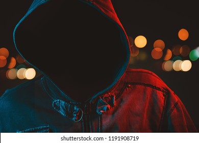 Faceless hooligan with hoodie in urban surrounding, low key portrait of hooded male person at city streets at night