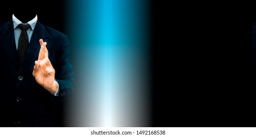 Faceless industrialist with crossed fingers against a black background wearing a blue colored suit with the concept of Good luck or dishonesty or falsehood.