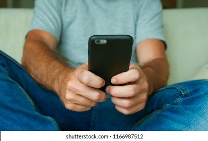 faceless lifestyle portrait with close up hands of young man holding mobile phone sitting relaxed at home sofa couch using internet social media app on smartphone networking and texting