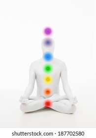 faceless man dressed in white sitting in yoga lotus position with chakra colored graphics
