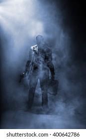 Faceless man holding a gun and a briefcase standing in haze.
