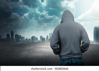 Faceless man in hood on the rooftop with city background