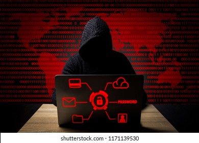 Faceless man in a hooded robe sits at a table with a laptop. The