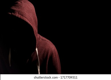 Faceless man in a hoody in dark shadows to disguise face