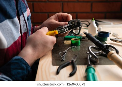 Faceless man stripping off wires while soldering them at table