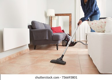 Faceless middle section of young woman using vacuum cleaner in home living room floor, doing cleaning duties and chores, meticulous interior. Young female working on house spring cleaning, indoors.