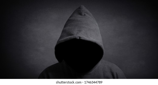 faceless person wearing black hoodie hiding face in shadow - mystery crime conspiracy concept
