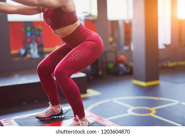 Faceless shot of athletic woman in sportswear doing squats in sunlight in gym