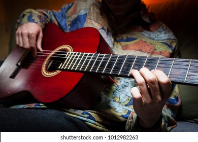 Faceless shot of a guitar performer while plays an acoustic guitar with vintage colorful shirt on a dark and warm background. Flamenco music guitarist playing concept.