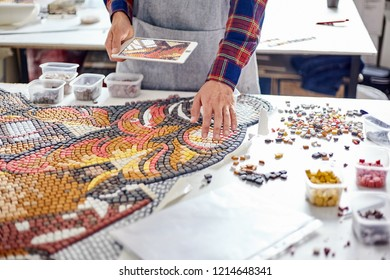 Faceless shot of man in apron standing at table in workshop and composing beautiful mosaic in daylight